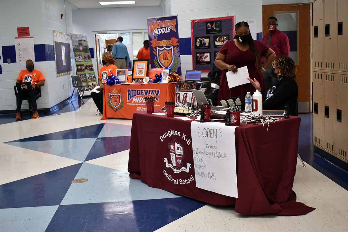 A maroon table for Douglass Optional School and Ridgeway Middle sit in a school hallway with blue and white tile. The desks are staffed by two people each, wearing their school's colors.