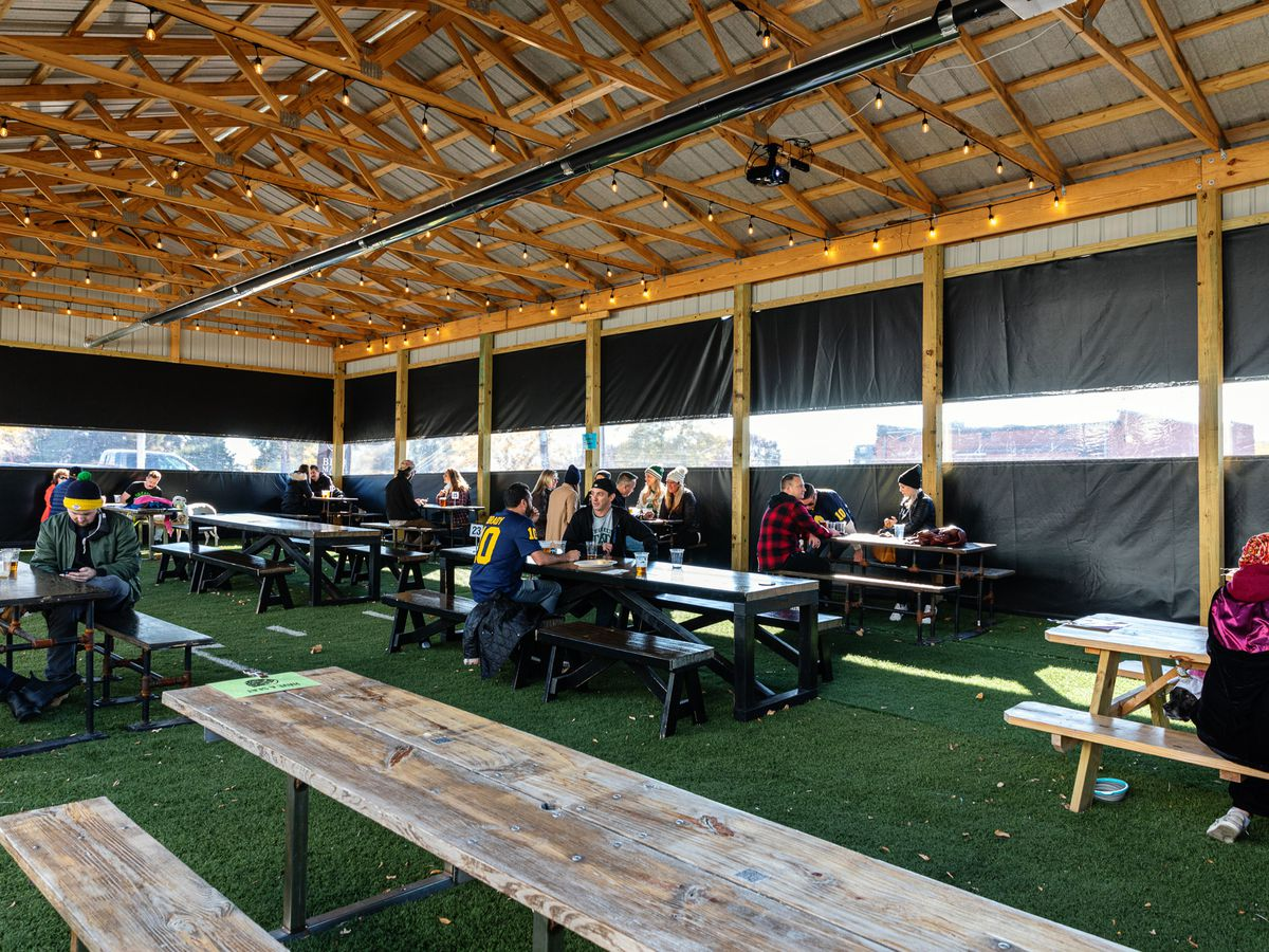 Customers sit at distanced picnic tables inside a partially enclosed pole barn in the Batch Brewing Company parking lot. The picnic tables are on top of astro turf.