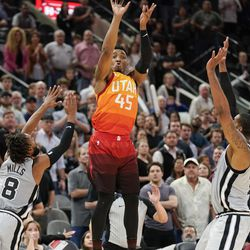 Utah Jazz's Donovan Mitchell (45) shoots a 3-point basket between San Antonio Spurs' Patty Mills (8) and LaMarcus Aldridge to tie the score at the end of the fourth quarter of an NBA basketball game, Friday, March 23, 2018, in San Antonio. San Antonio won 124-120 in overtime. (AP Photo/Darren Abate)