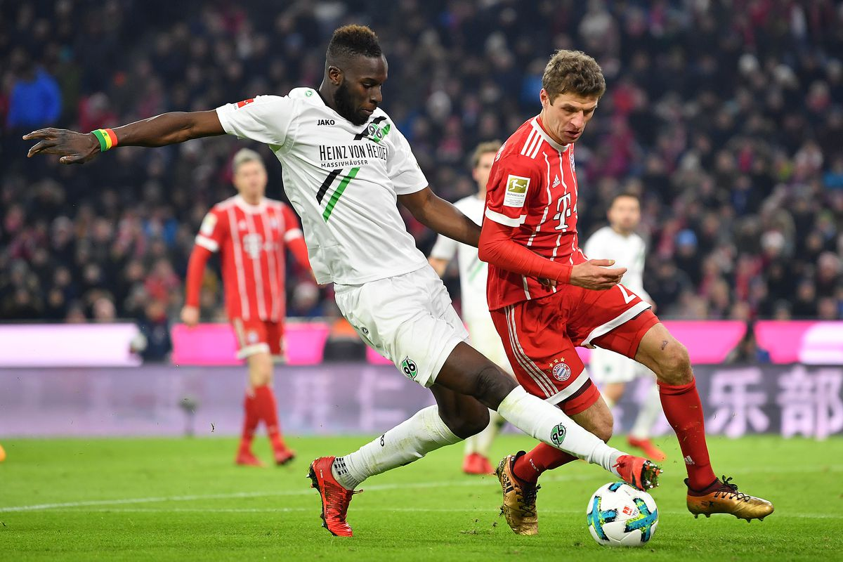MUNICH, GERMANY - DECEMBER 02: Salif Sane of Hannover (l) fights for the ball with Thomas Mueller of Bayern Muenchen during the Bundesliga match between FC Bayern Muenchen and Hannover 96 at Allianz Arena on December 2, 2017 in Munich, Germany. (Photo by Sebastian Widmann/Bongarts/Getty Images)