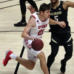 Utah Utes forward Riley Battin (21) dribbles past Colorado Buffaloes guard D'Shawn Schwartz (5) during a men's basketball game at the Huntsman Center in Salt Lake City on Monday, Jan. 11, 2021. Utah lost 58-65.