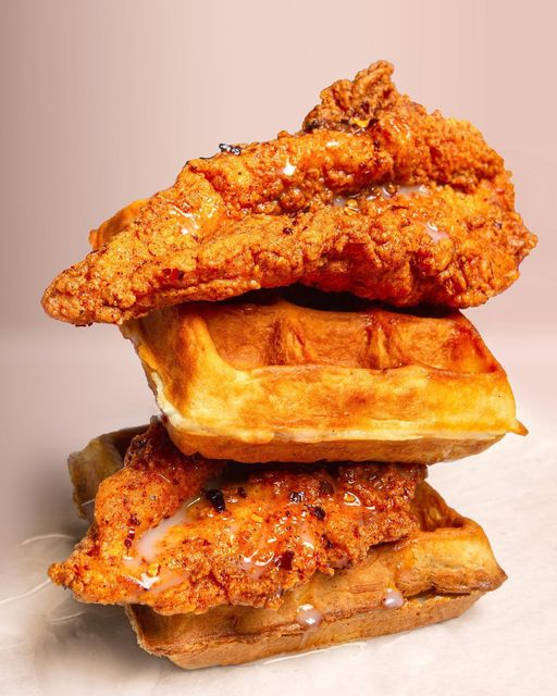 A stack of golden, crispy looking fried chicken and waffles from Ali's Chicken and Waffles in City Heights, San Diego, California.