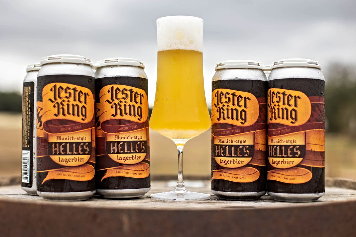 """A tall wine-like glass full of golden beer with a top of foam flanked by tall cans of beer that read """"Jester King, Munich-style Helles Lagerbier"""" on a wooden barrel"""
