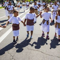 """Kids in the """"Pioneers 50th Year in America"""" group hold hands as they walk through the Days of '47 Union Pacific Railroad Youth Parade held Saturday, July 18, 2015, in Salt Lake City."""