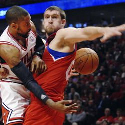 Chicago Bulls point guard C.J. Watson passes around the back of Philadelphia 76ers' Spencer Hawes during Game 1 in a first-round NBA basketball playoff series against the Philadelphia 76ers, Saturday, April 28, 2012, in Chicago. The Bulls won 103-91.