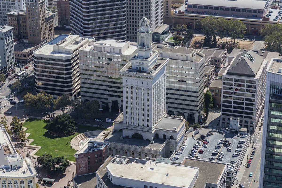 Afternoon aerial view of Oakland city hall, a tall white building with a spire.
