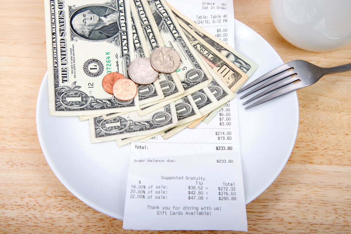 A stock photo of $38 dollars and change on a plate with a bill suggesting tips amounts and a metal fork.