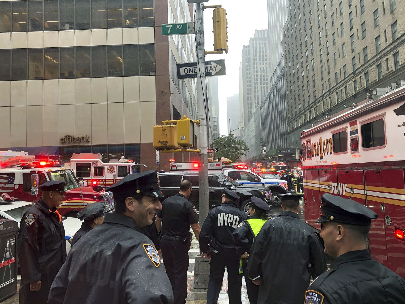 New York police officers monitor the streets near 51st Street and 7th Avenue, Monday, June 10, 2019, in New York, where a helicopter was reported to have crash landed on top of a building in midtown Manhattan.