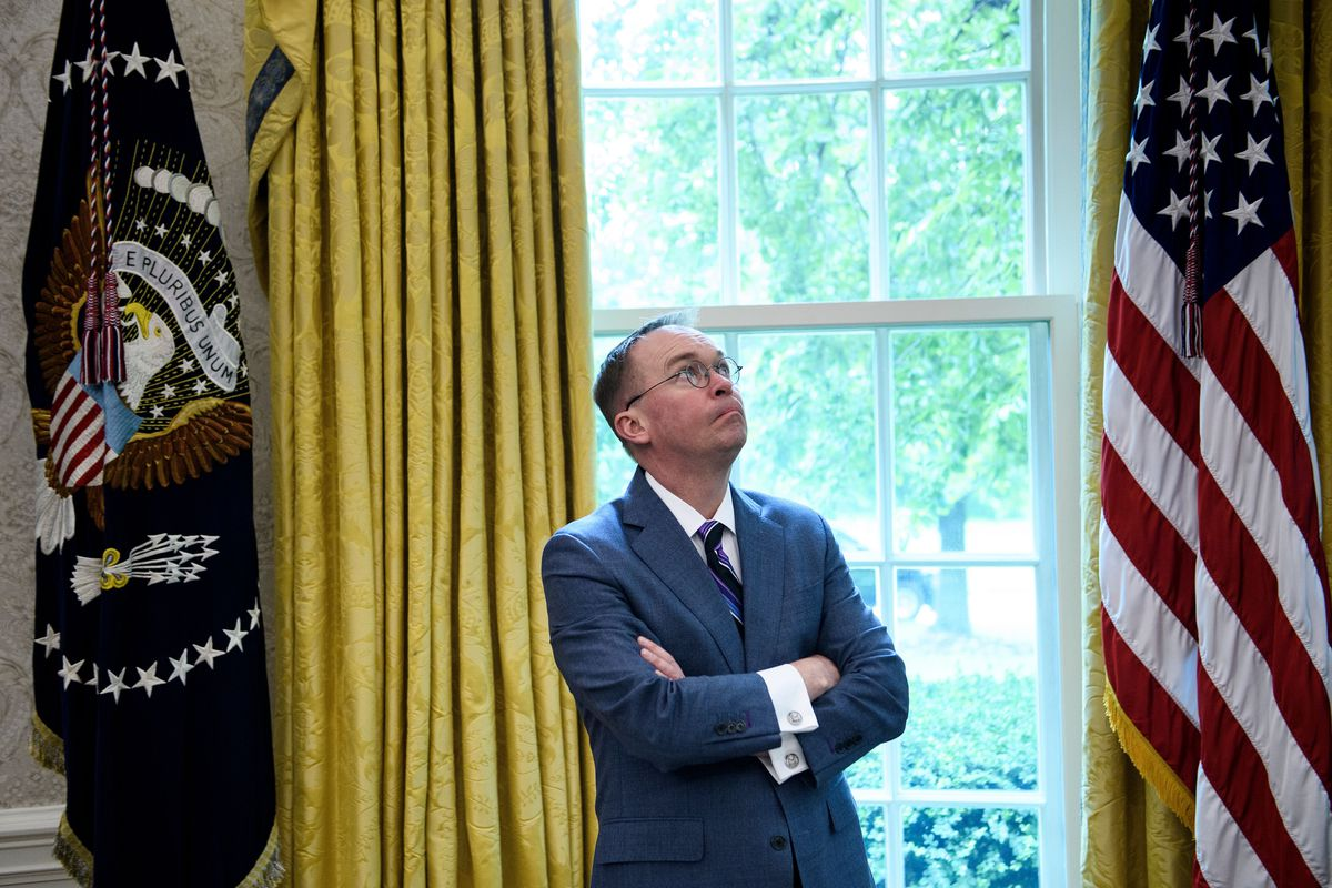 White House acting Chief of Staff Mick Mulvaney standing in the Oval Office between the US flag and the presidential flag.