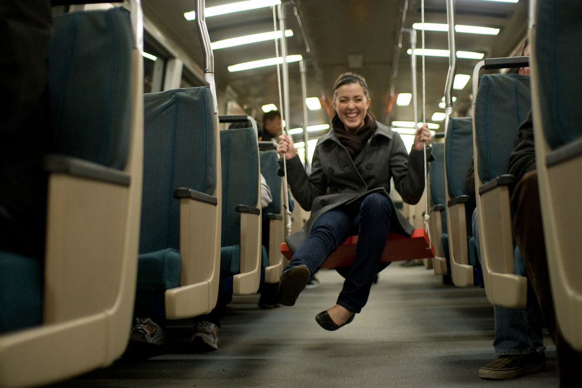 Woman swinging on BART train on a swing in betweem the seats on the aisle.