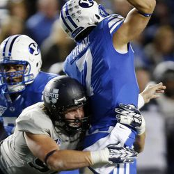 Jordan Nielsen (97) of the Utah State Aggies tackles Christian Stewart (7) of the Brigham Young University Cougars as he passes during NCAA football in Provo, Friday, Oct. 3, 2014.