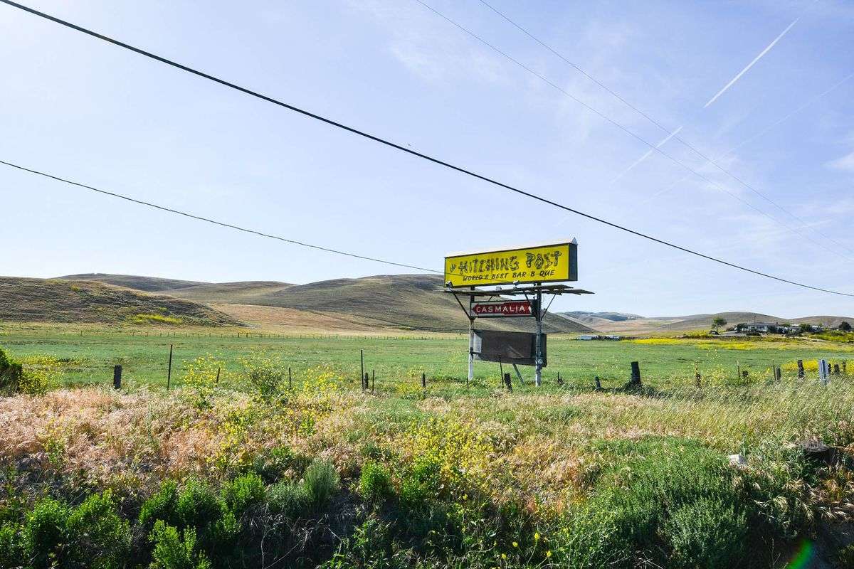 A yellow sign in the middle of nowhere points to The Hitching Post.