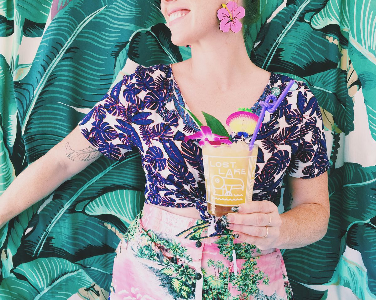 A woman wearing tropical clothing, holding a drink from Lost Lake Tiki bar