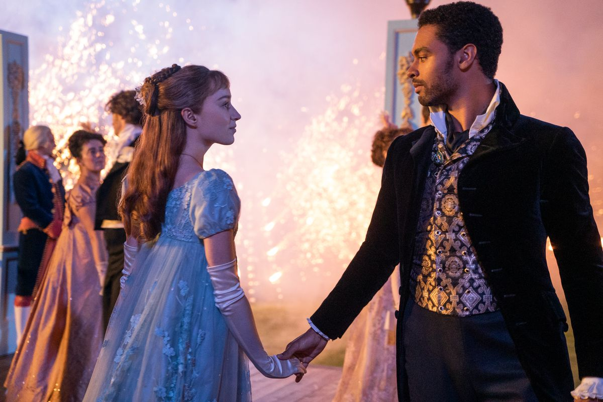 A couple in Regency-era dress take hands to dance.