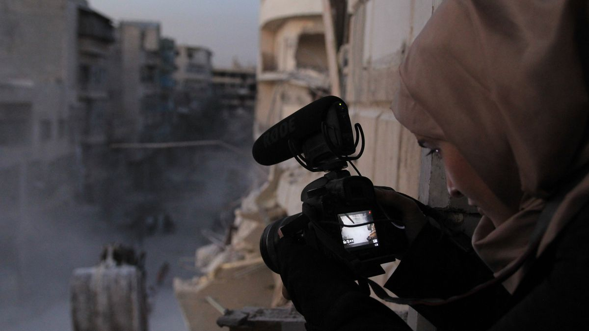 a woman in a hijab holds a video camera in a destroyed city in For Sama