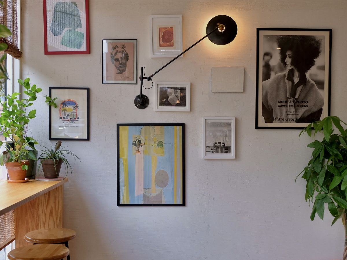 Artwork hung up on a white wall with a light wooden bar along the window to the left of the photo.
