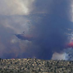 An aerial tanker drops fire retardant on a wildfires threatening homes near Yarnell, Ariz., Monday, July 1, 2013. An elite crew of firefighters was overtaken by the out-of-control blaze on Sunday, killing 19 members as they tried to protect themselves from the flames under fire-resistant shields. (AP Photo/Chris Carlson)