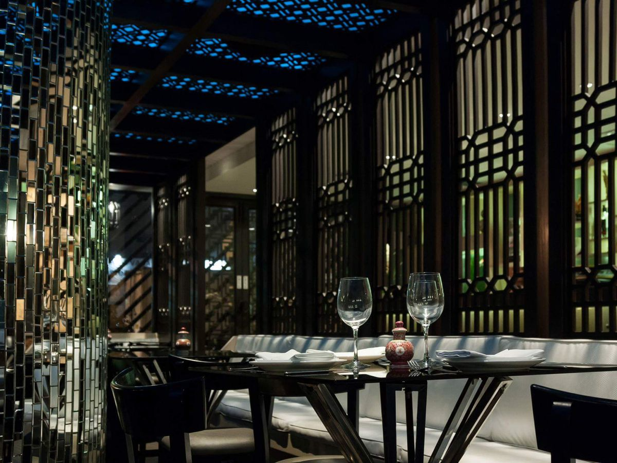 The dark, alluring interior of Chifa Titi, with a two-top and wine glasses in the foreground, tall patterned windows, and shining, crystal-like decorations.