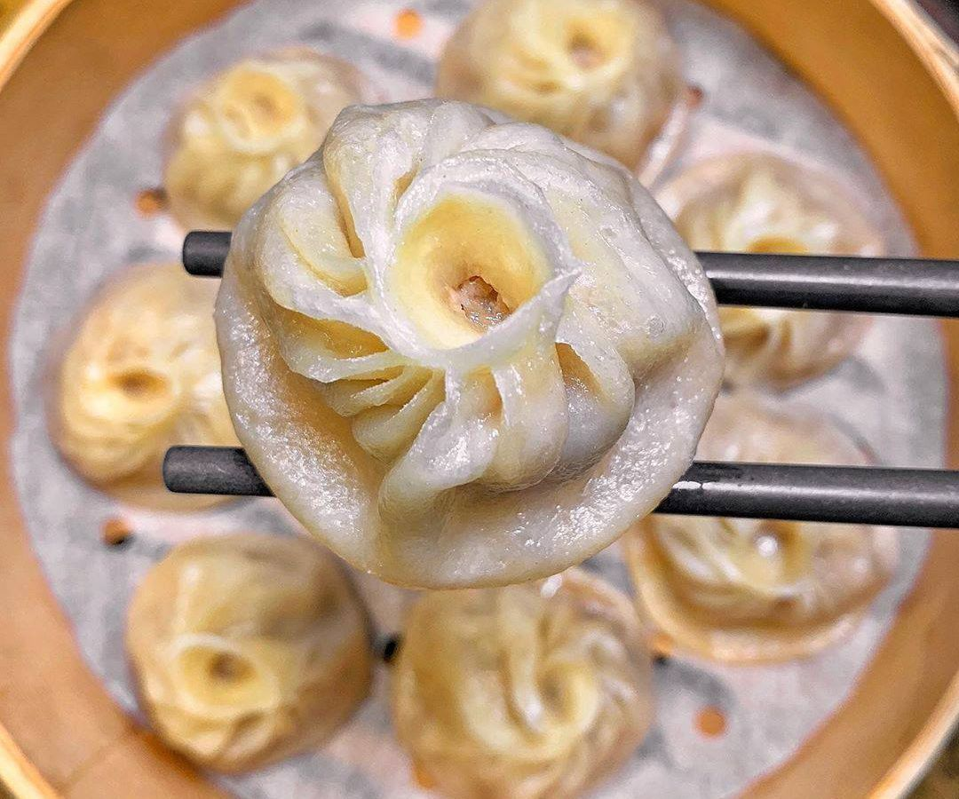 A plate of dumplings with one held on a set of chopsticks