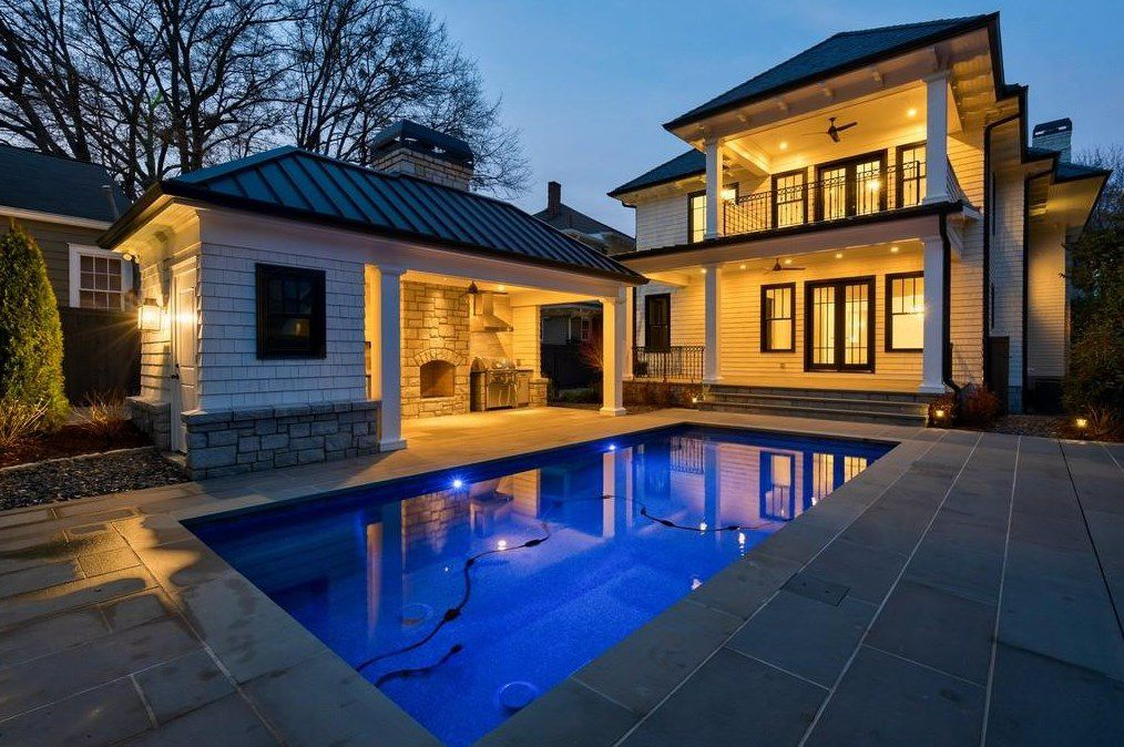 A pool behind a huge white home shown at night.