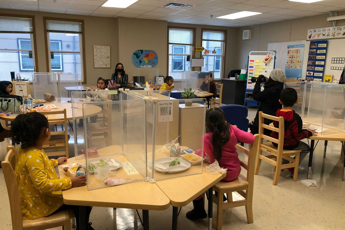 Students eat lunch behind Plexiglass shields at Dawes Elementary in Chicago's Ashburn neighborhood. Chicago reopened schools Monday to about 6,000 students despite opposition to the plan from its teachers' union.