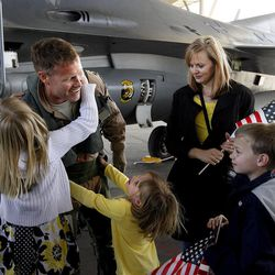 Lt. Colonel Chris Bailey of the 388th Fighter Wing is greeted by his family, daughters Cori and Erin, wife Monica and son Nate,  at Hill Air Force Base in Layton after a nearly seven month deployment to Bagram Airfield, Afghanistan on Friday, April 15, 2011.