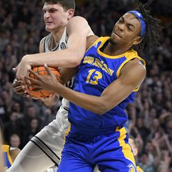 Utah State center Trevin Dorius and San Jose State guard Seneca Knight (13) struggle for a rebound during the first half of an NCAA college basketball game Tuesday, Feb. 25, 2020, in Logan, Utah.