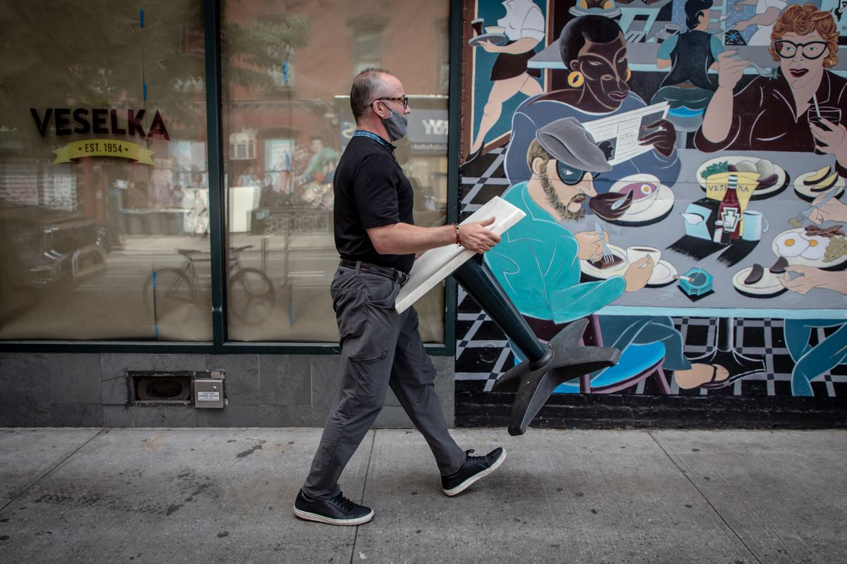 Jason Birchard carries a table past a mural on Veselka's Ninth Street exterior