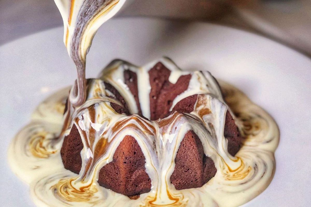 Sticky toffee pudding with toffee sauce and custard poured from on high onto a white plate