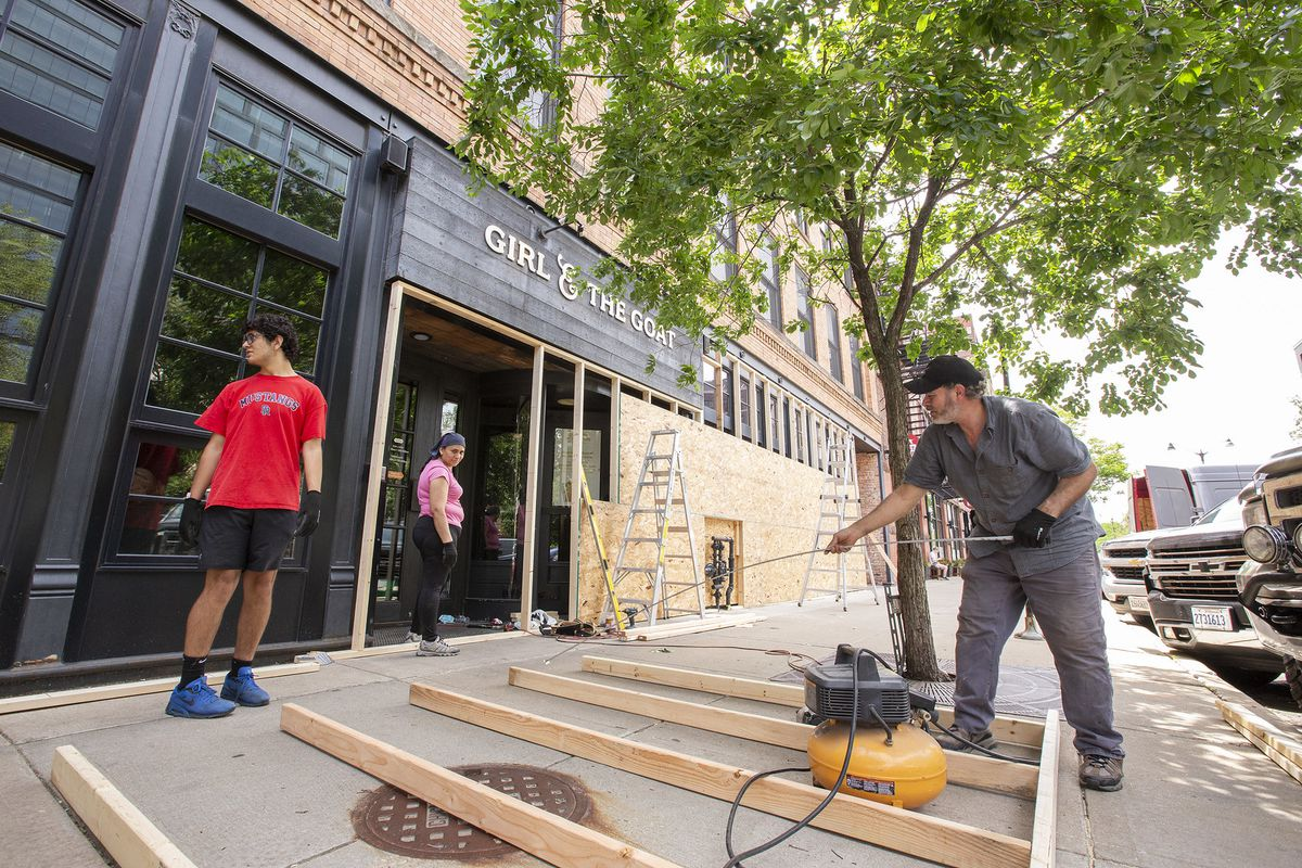 Crews putting up wooden frames to cover windows at a restaurant on a sidewalk.
