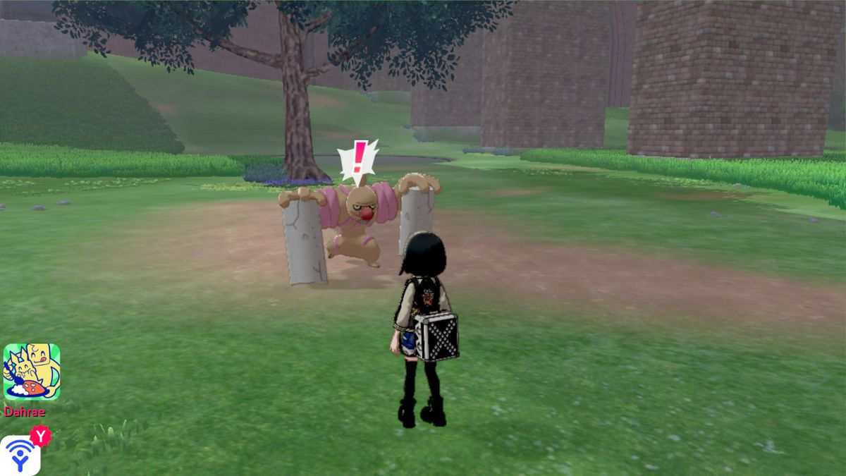 A conkeldurr stares at a Pokémon trainer in the Wild Area.