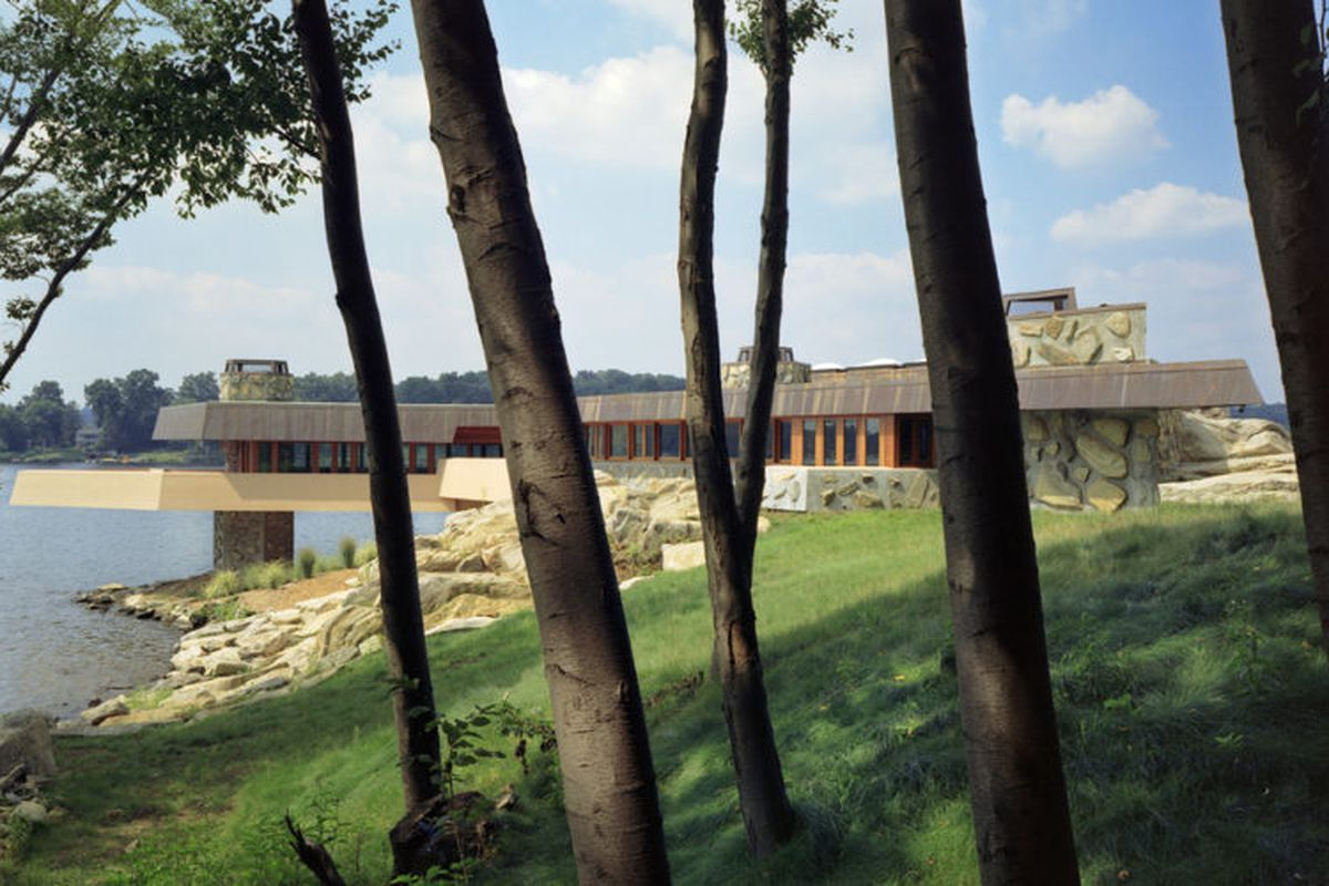 A low, flat-roofed home with stone walls and a wraparound balcony cantilevers off a rocky shore.