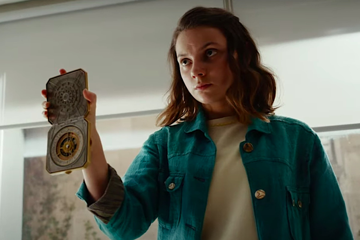 Lyra in His Dark Materials holds up her magical alethiometer like it's a police badge
