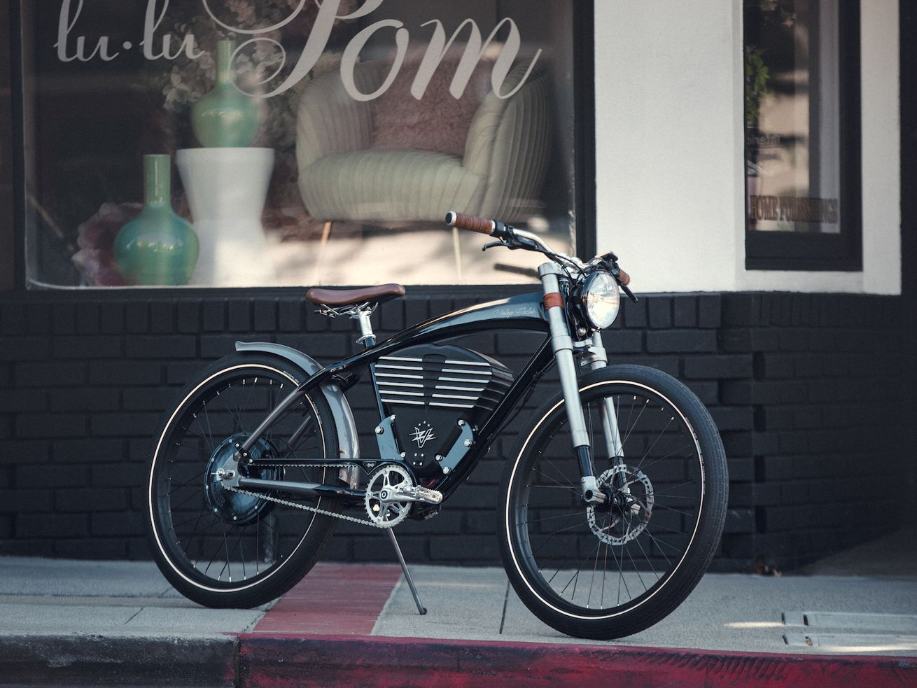 Suave electric bike with swoopy black frame parked on a sidewalk in front of a store.