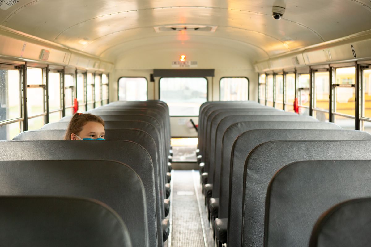 Students wait inside a near-empty bus after dismissal.