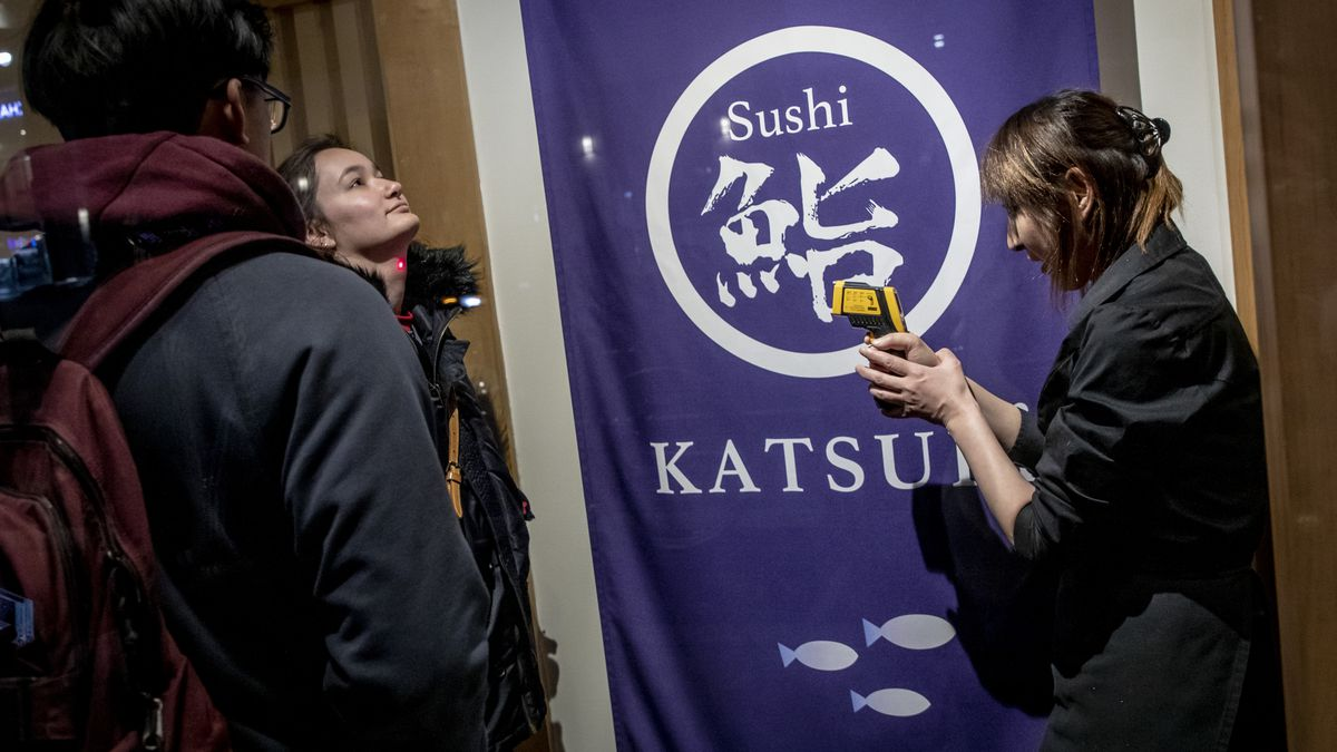 A staffer at Sushi Katsuei checking diners' temperatures before they sit down in the dining room