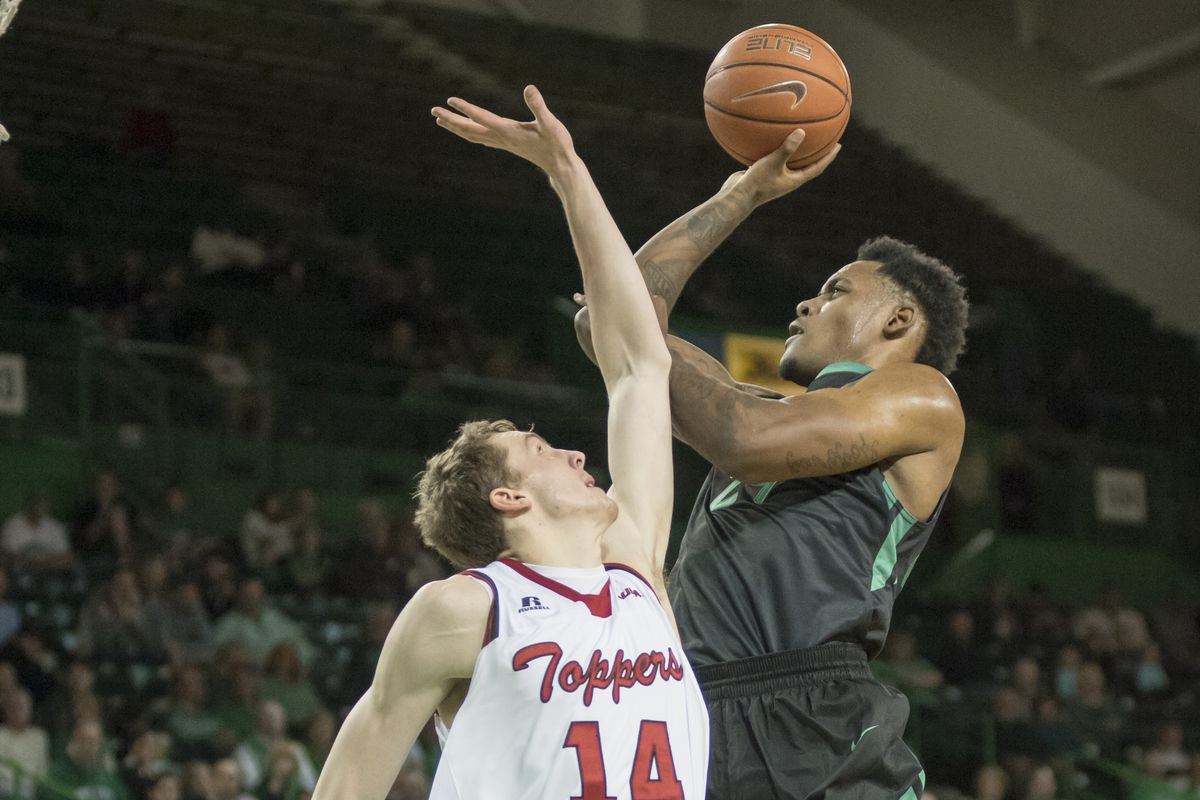 James Kelly (24) sails past Ben Lawson (14) in the Herd's 94-76 win over the Hilltoppers.