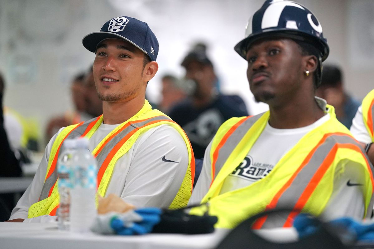 Los Angeles Rams rookies S Taylor Rapp, left, and CB David Long, Jr., watch a video about the Rams' new stadium opening for the 2020 season before touring the construction site, Jun. 7, 2019.