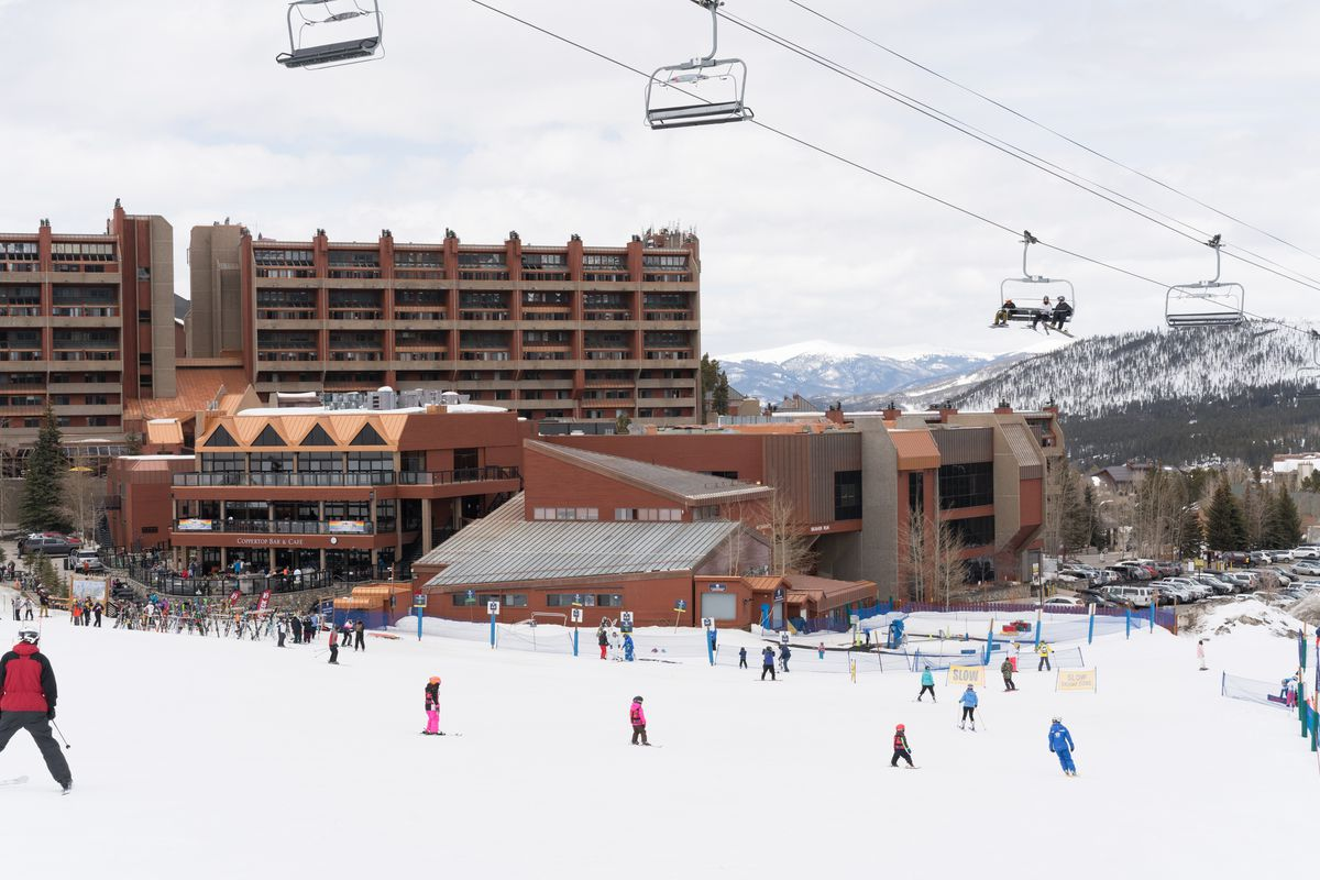 Skier with buildings behind and the ski lift above.