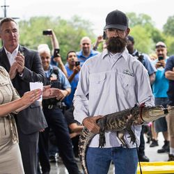 Florida alligator expert Frank Robb receives a round of applause Tuesday as he shows off the alligator he rescued from the Humboldt Park Lagoon.