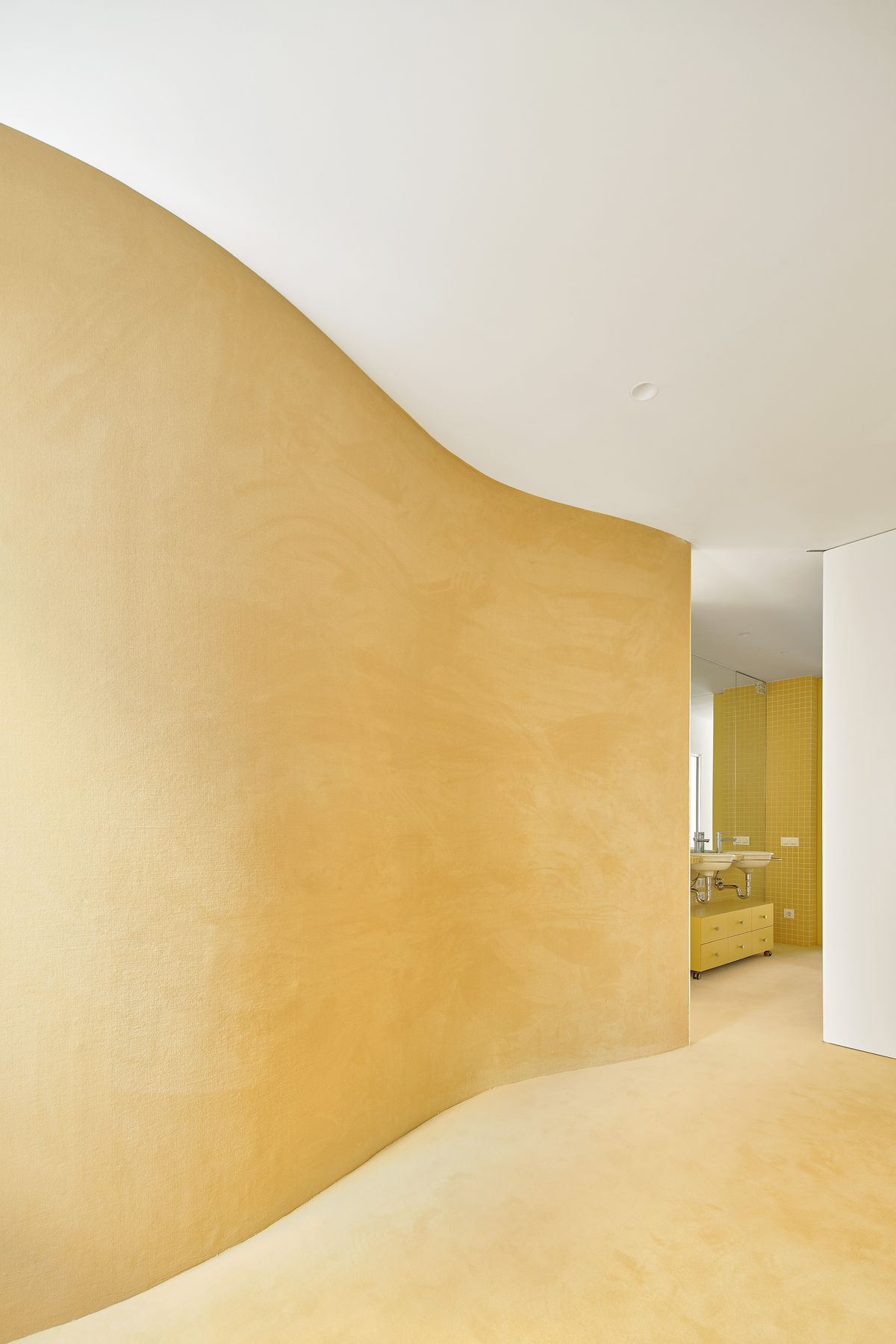 Curved yellow wall next to yellow carpet.