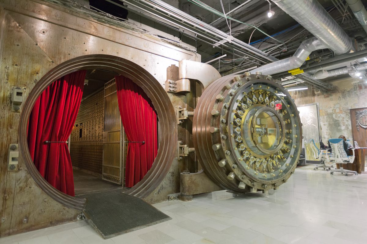 A swanky conference room within an old bank vault walled with long-locked deposit boxes