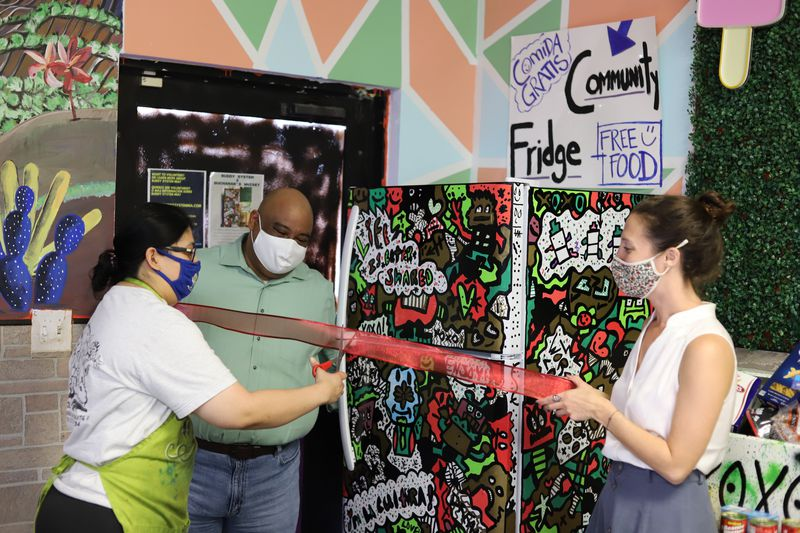 A worker in an apron cuts a ceremonial red ribbon held by two other workers across the front of a community fridge.