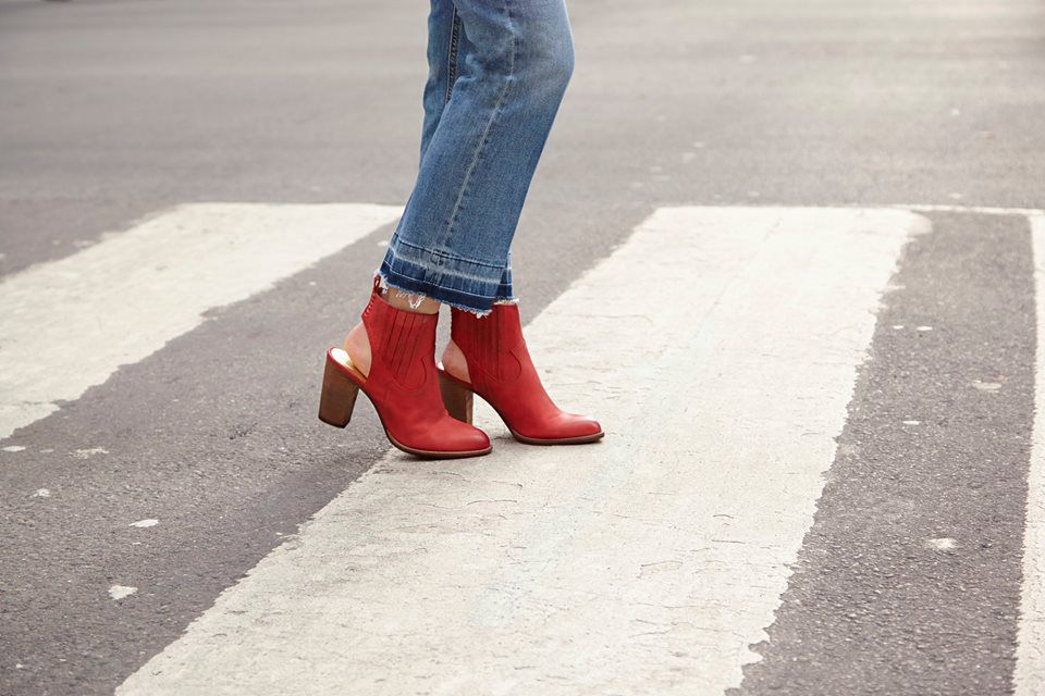 A woman from the knee down in jeans and red shoes in a crosswalk.