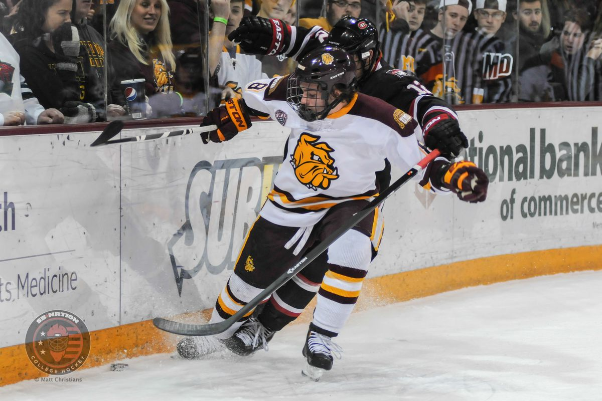 Kyle Osterberg battles for the puck against SCSU