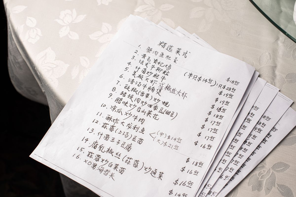 A stack of handwritten menus in Chinese atop a table.