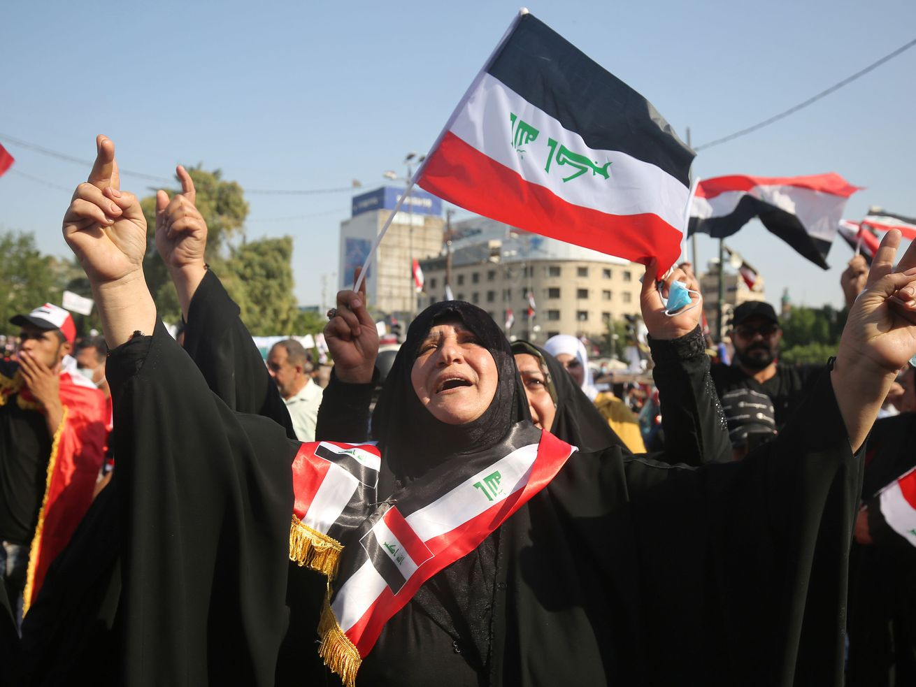 An Iraqi protester in a burqa raises their arms while others wave flags in Baghdad's Tahrir Square.