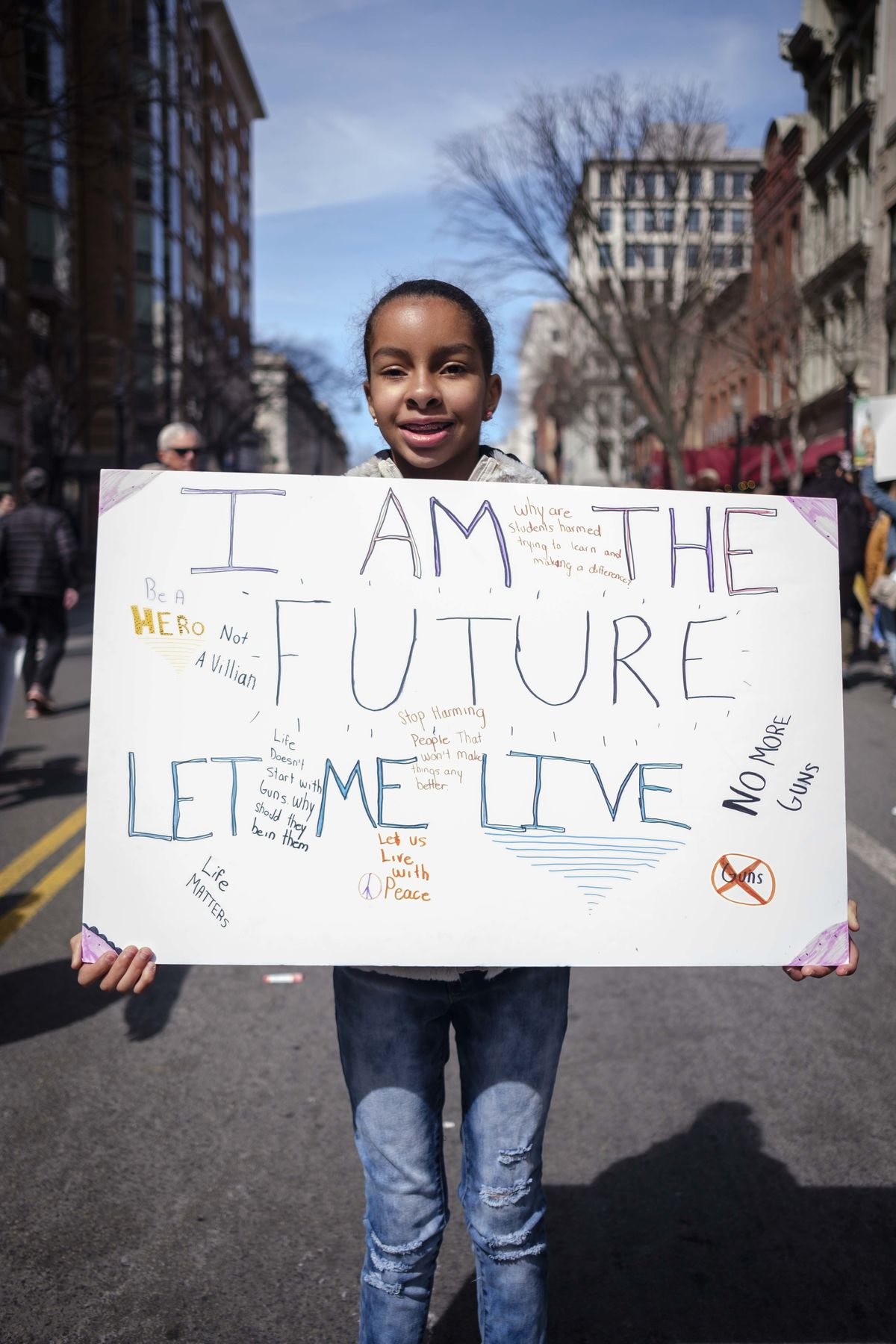"""A girl carries a sign that says, """"I am the future, let me live."""""""
