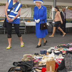 Executive Director of Kensington and Chelsea Council Sue Harris, left, shows Queen Elizabeth II donations of aid made by members of the local community during a visit to the Westway Sports Centre which is providing temporary shelter for those who have been made homeless by the fire at Grenfell Tower,  in London,  Friday June 16, 2017. Relatives of those missing after a high-rise tower blaze in London are searching frantically for their loved ones, as the police commander in charge of the investigation says he hopes the death toll will not rise to three figures.