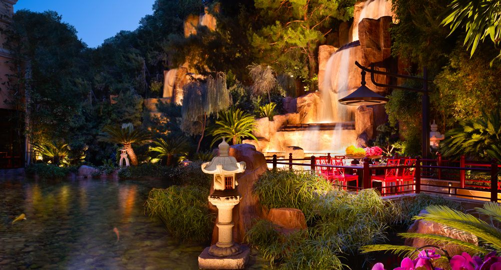 A patio in a lake with a waterfall at night